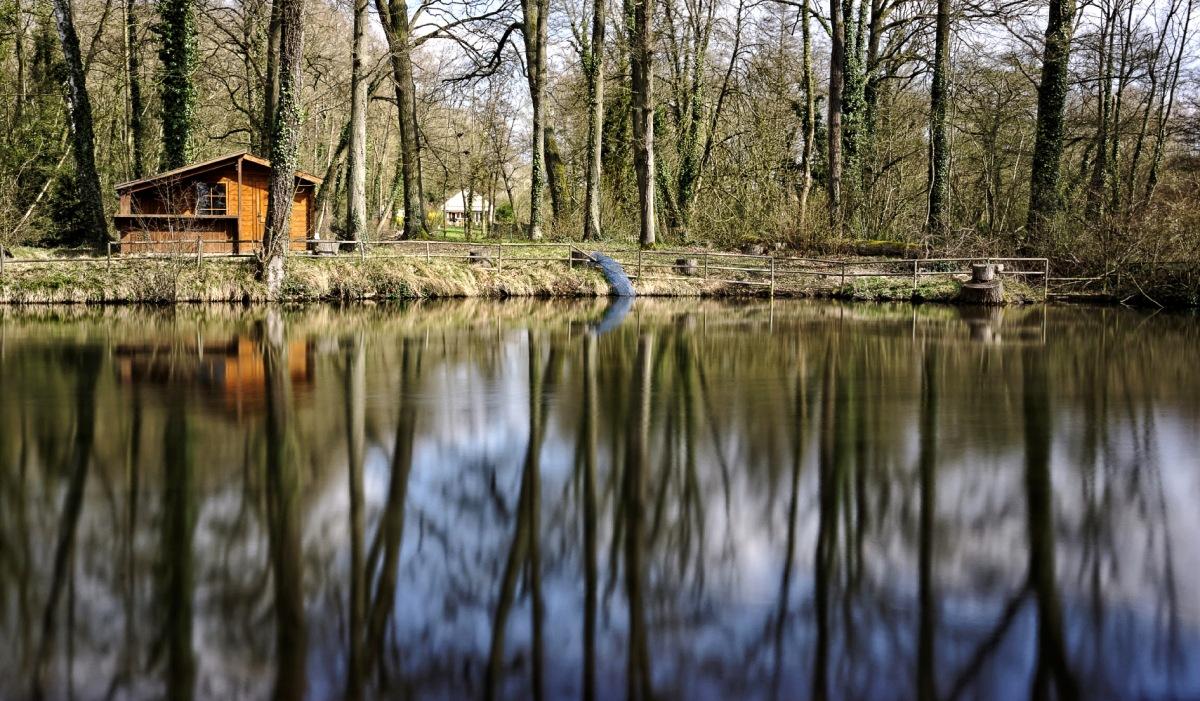 chalet de bois, filet bleu, au bord de l'eau, au fil de l'eau, étang, reflets, pose longue