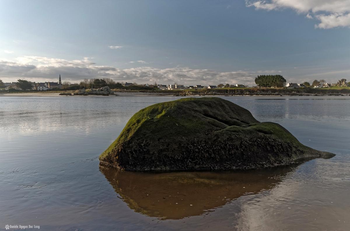 soleil levant sur les rochers au fond de la baie de Guissény et sur le bourg