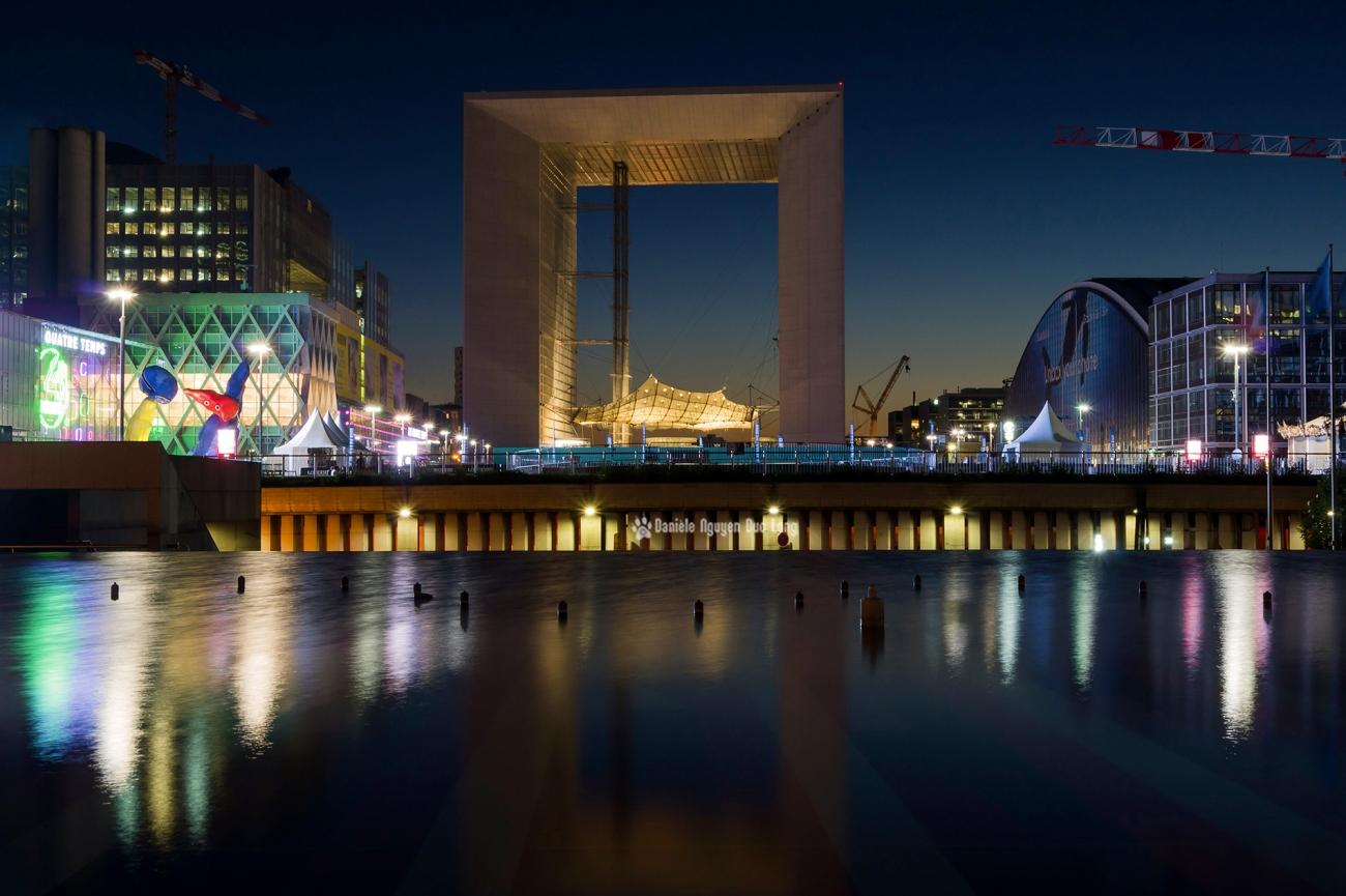 début de nuit sur l'Arche de la Défense et reflets fontaine Agam