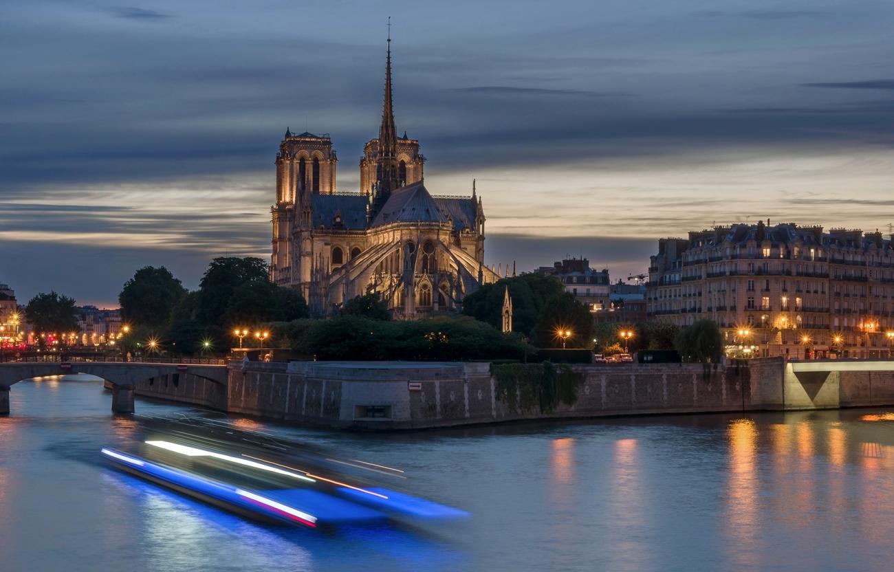 début de nuit sur notre Dame de Paris, île de la Cité, Paris, Notre Dame de Paris illuminée, bateau mouche en pose lente sur la Seine